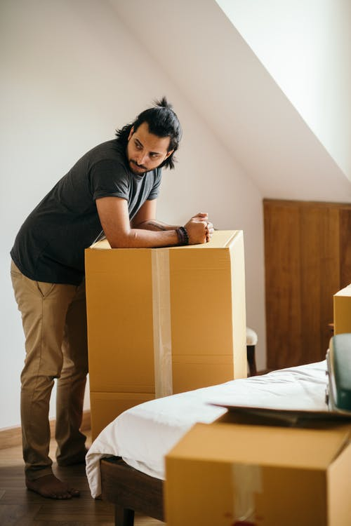 Side view of full body barefoot ethnic man in casual clothes leaning on big cardboard box with stuff from home for moving and looking away