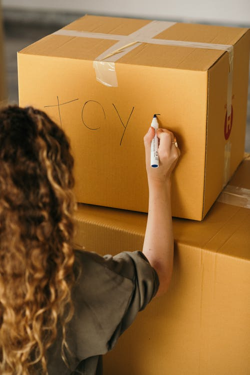 Back view of crop faceless female in casual wear labeling packed cardboard box with marker while moving house