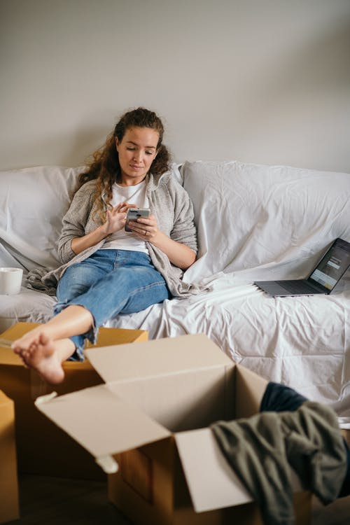 Full length of serious young female in casual clothes sitting on covered sofa with laptop and cup of coffee using smartphone in new house with cardboard boxes