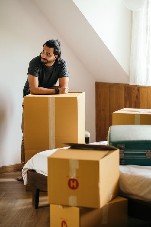 Thoughtful ethnic man standing in new house leaning on unpacked carton box
