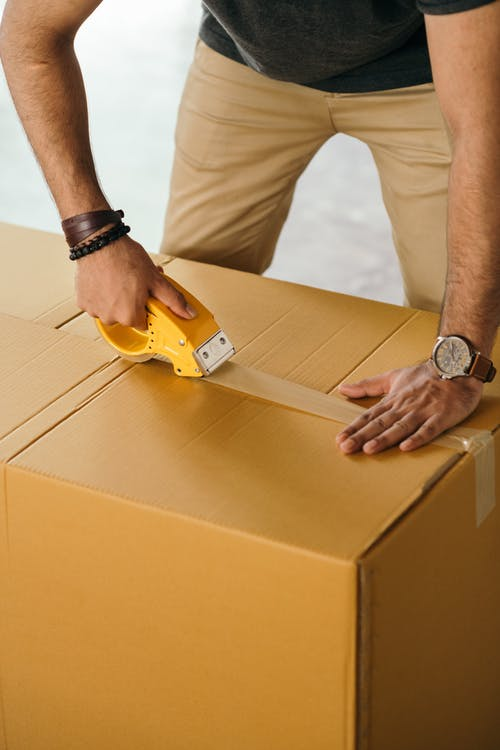 Unrecognizable man sealing box with duck tape while preparing for moving out