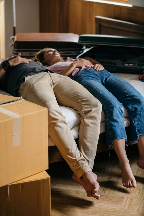 Tired couple lying on bed near boxes