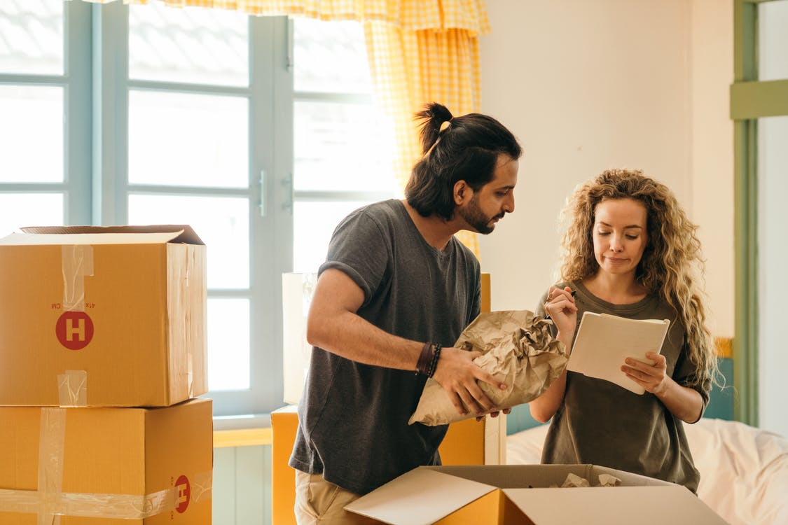 Happy couple unpacking boxes in new home