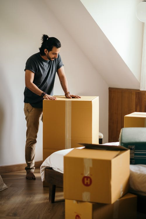 Young man packing cardboard boxes at home