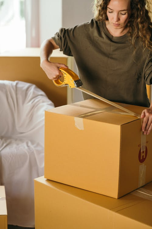 Crop female wearing casual clothes standing while packing carton boxes with scotch tape in modern apartment during preparing for relocation