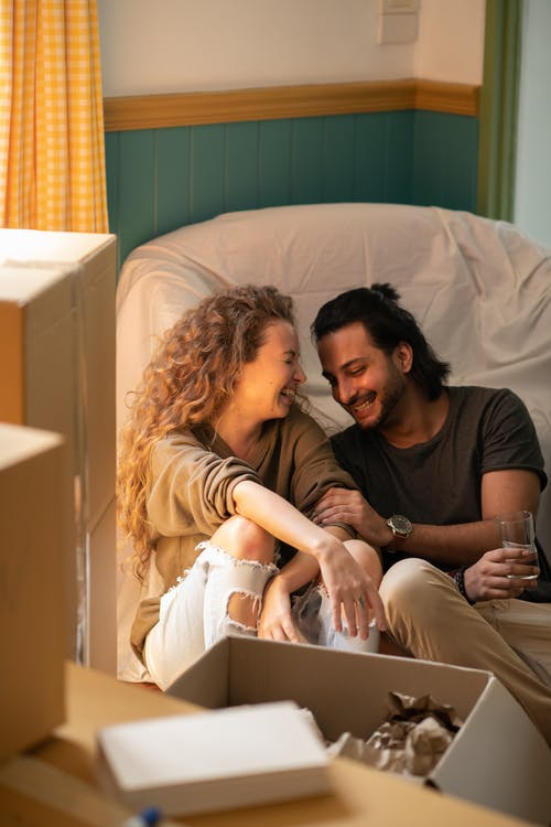 Happy couple laughing while embracing each other among carton boxes