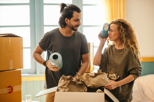 Satisfied adult bearded ethnic man and playful woman with curly hair wearing casual t shirts unboxing ceramics for home decoration from carton boxes while moving in new apartment