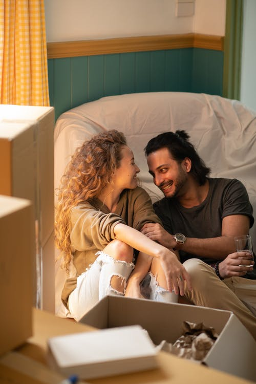 Laughing young ethnic man drinking glass of water while sitting on floor together with girlfriend in casual clothes in room with covered furniture while moving in own apartment and unboxing stuff