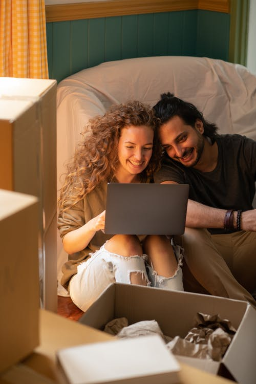 Happy diverse couple using laptop while relocating into new apartment