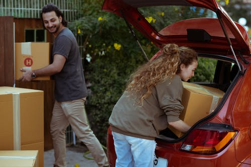 Young woman with curly hair getting carton box out from trunk of automobile while cheerful ethnic man carrying box into new home in suburb or countryside area