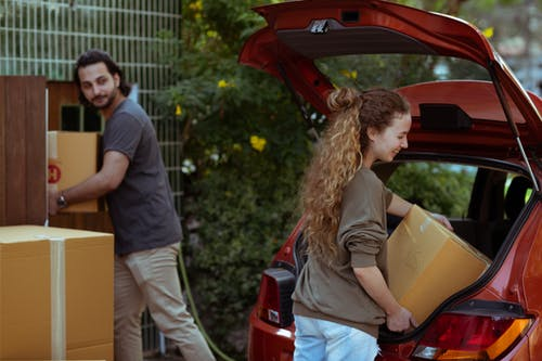 Couple getting carton boxes out of red car while relocating in new home