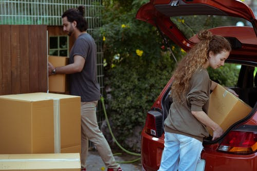 Diverse couple getting carton boxes out of car while relocating in suburb or countryside