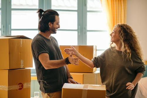 Happy diverse couple among carton boxes in new home