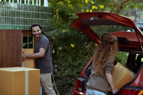 Happy couple in casual clothes moving personal items in carton boxes from car trunk to new house