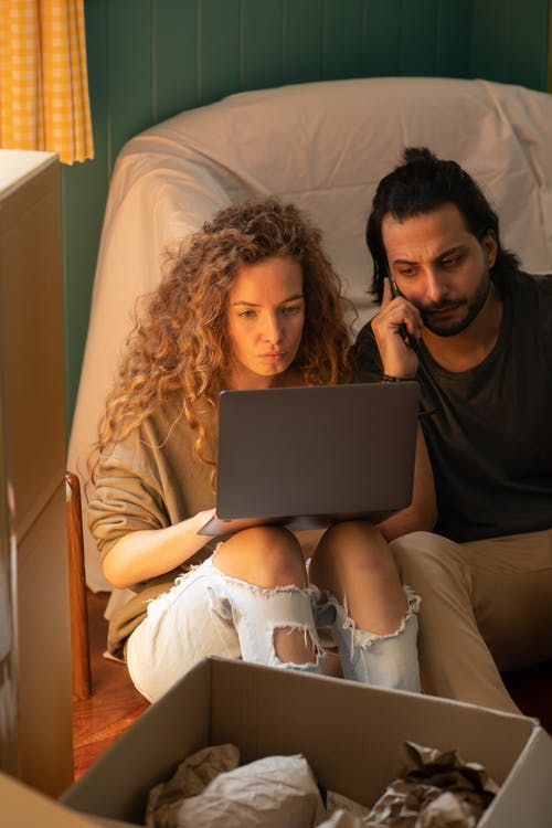 From above of concentrated couple in casual clothes sitting on floor among carton boxes and covered with sheet arm chair while using netbook and calling by mobile phone
