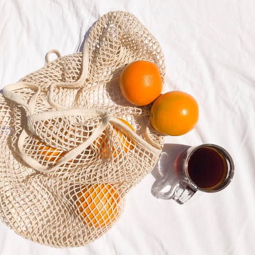 Top view of colorful ripe whole oranges with shiny surface in food net near glass cup of hot black tea on creased sheet at home