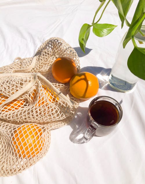 Black tea with fresh oranges and vase with plant