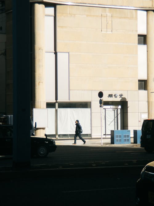 Side view of anonymous male walking along pavement near concrete building and cars in city in sunny day