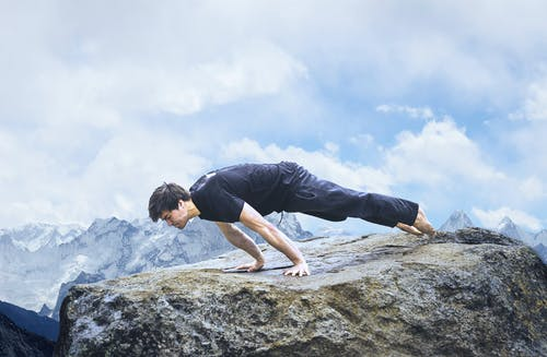 Fit man balancing on arms in mountains under cloudy sky