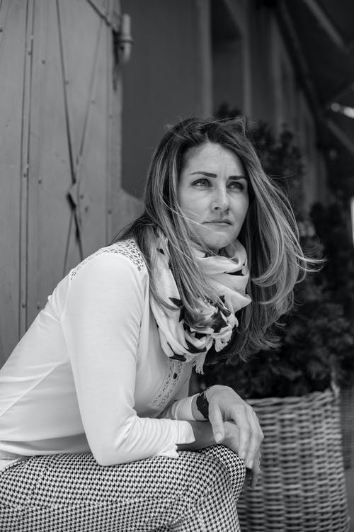 Black and white shot of pensive young female in smart casual outfit sitting outside modern building and looking away in deep thoughts