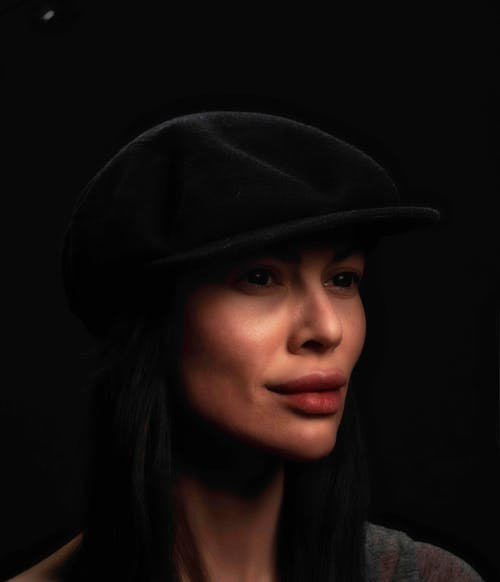 Positive woman in stylish hat in studio