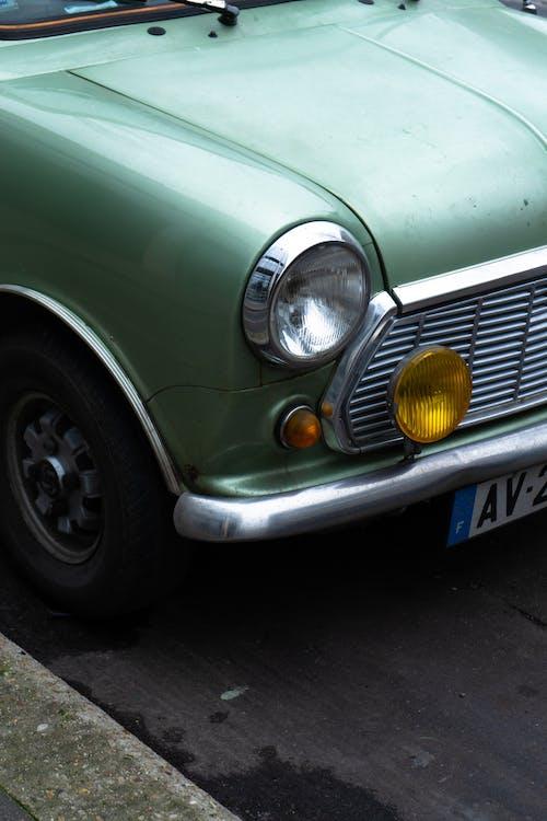 Vintage automobile headlight and hood of light green color parked on asphalt roadside