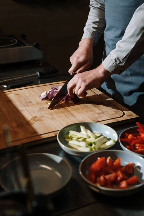 Person Slicing Vegetable on Chopping Board