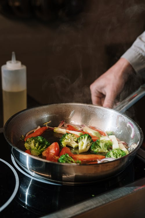 Person Holding Black Cooking Pan With Vegetable Salad