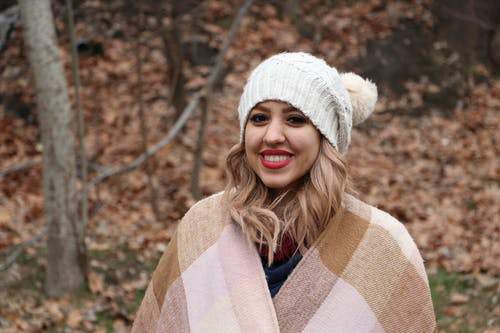 Woman in White Knit Cap and Brown and White Scarf