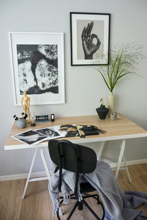 Chair and working desk with magazines and vases in cozy light room