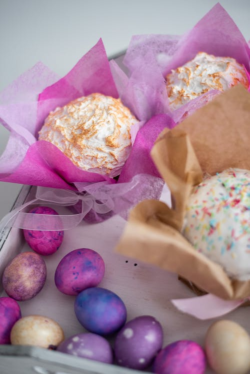 Colorful Easter eggs and wrapped meringue cakes in box