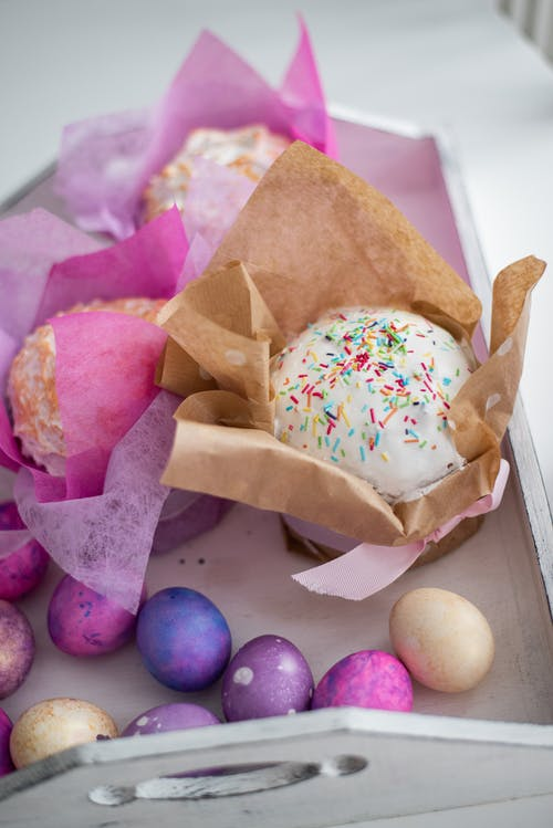 Easter box with delicious decorated cakes and scattered multicolored eggs