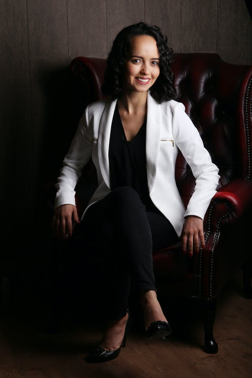 Stylish young businesswoman sitting in leather armchair