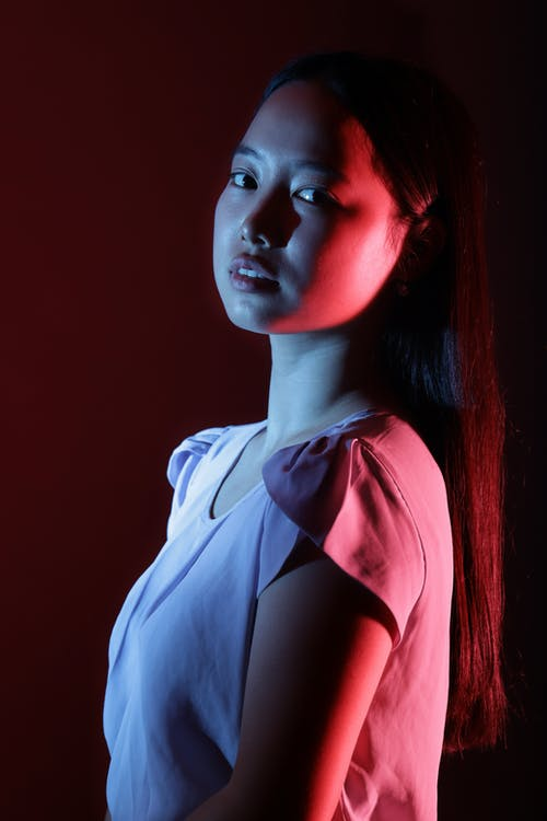 Young ethnic lady standing under neon illumination