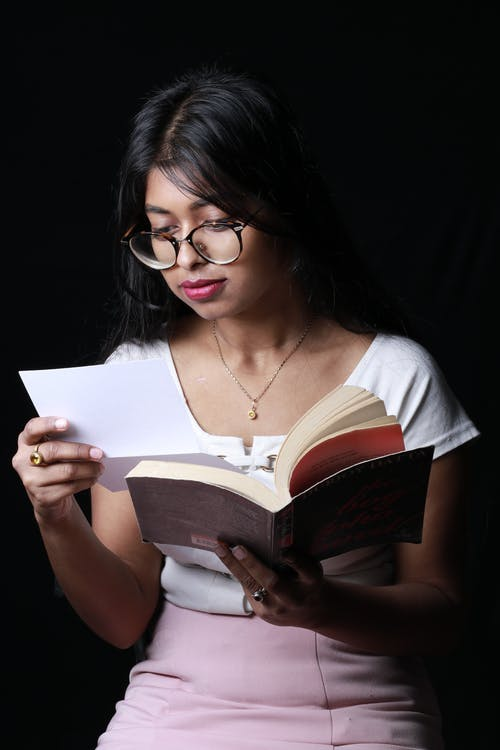 Focused young ethnic female student reading textbook