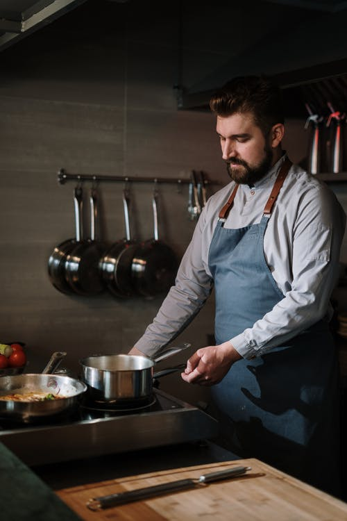 Man in White Dress Shirt and Blue Apron Holding Stainless Steel Cooking Pot