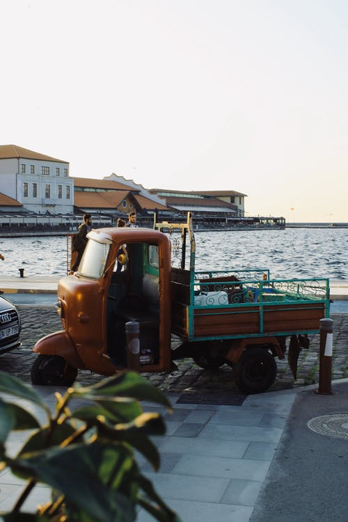 Vintage auto rickshaw truck parked on embankment near sea