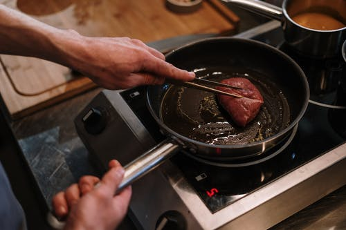 Person Cooking on Black Pan