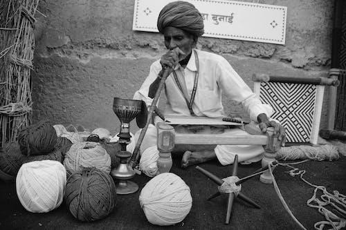 Elderly ethnic man smoking hookah and weaving traditional carpet on street