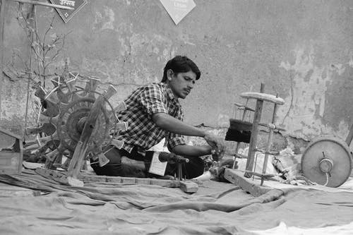 Serious ethnic man weaving textile on street