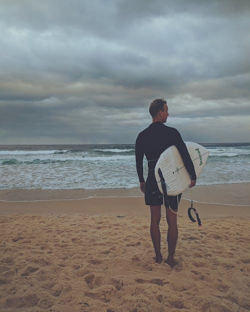 Anonymous male surfer standing on sandy seashore against overcast sky