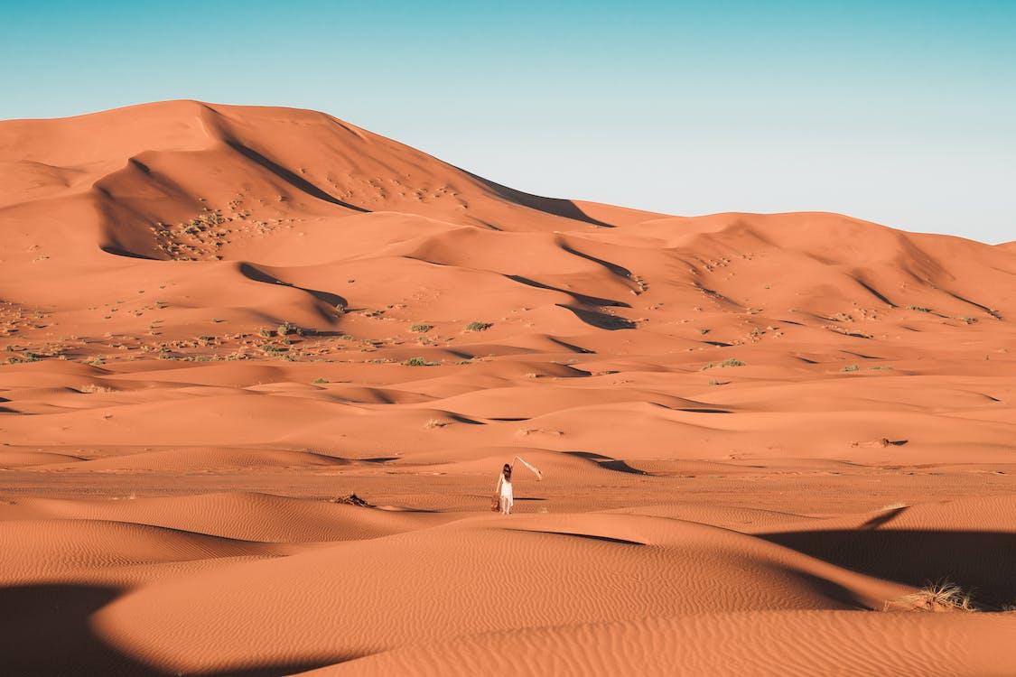 Person in White Shirt Walking on Desert