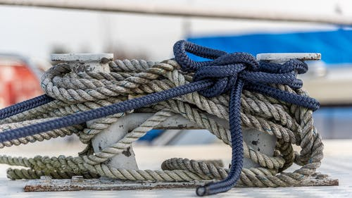 Close up of nautical knot ropes tied around metal bollard on modern ship deck