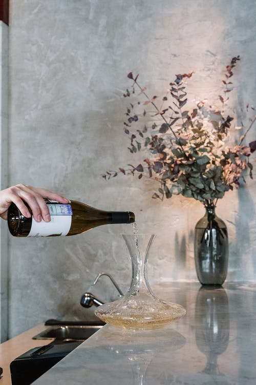 Person Pouring Wine on Clear Glass Bottle