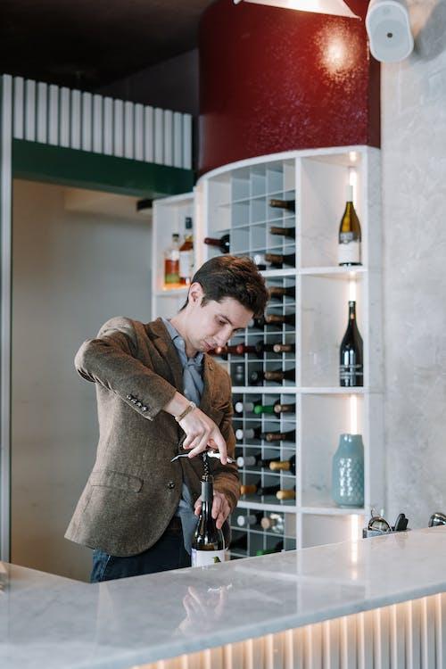 Man in Brown Coat Holding Bottle