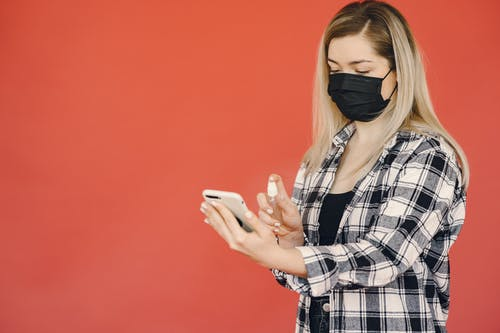 Young woman disinfecting smartphone during coronavirus pandemic
