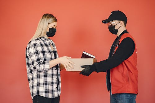 Side view of adult delivery man in protective mask and goggles with gloves giving carton parcel to woman in checkered shirt and medical mask isolated on red background illustrating concept of safety delivery during quarantine