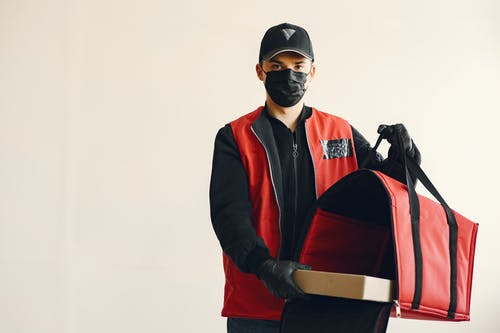 Young pizza delivery man in uniform and protective mask