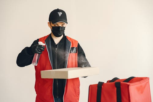 Male courier in cap and uniform wearing medical facial mask and gloves spraying antiseptic on carton pizza box against white background near thermo bag illustrating safety food delivery concept