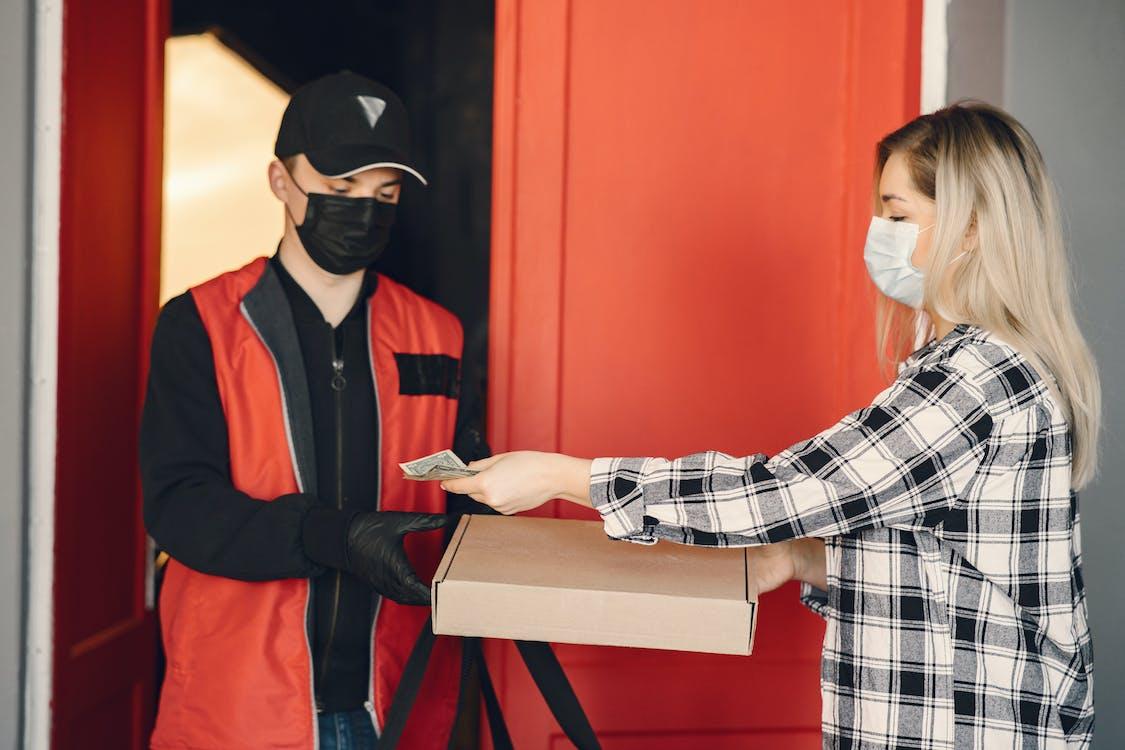 Young female customer receiving pizza during coronavirus pandemic quarantine